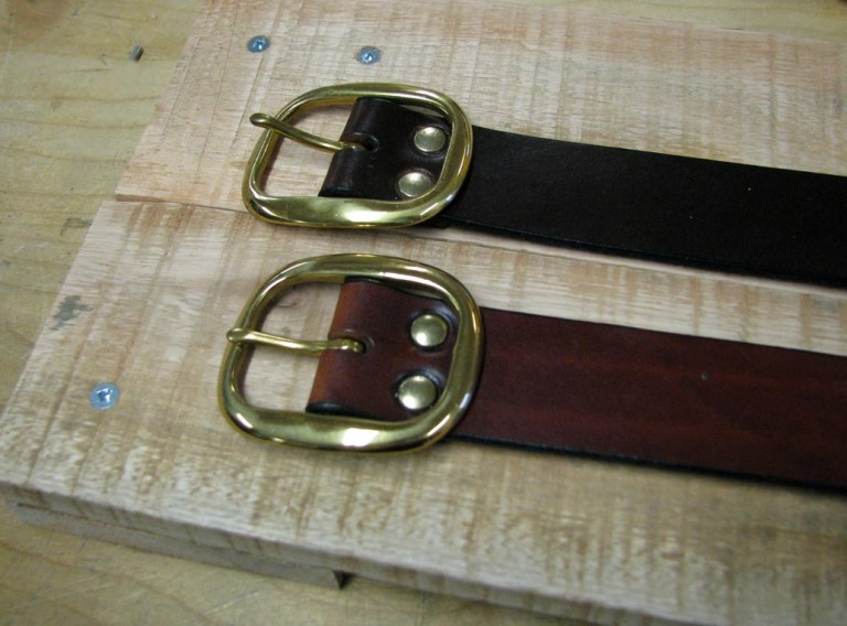 Solid leather belts with buckles secured by rivets